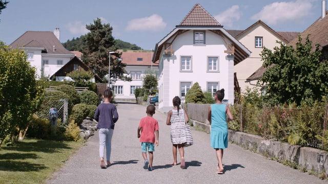 Vier dunkelhäutige Kinder gehen auf einer Dorfstrasse.