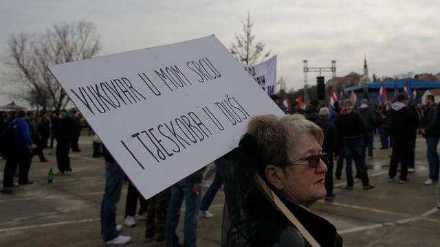 Eine Frau hält an einer Demo ein Schild gegen die Einführung des Kyrillischen in Kroatien.