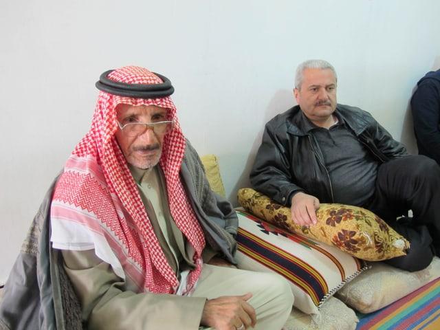 Zwei Männer auf dem Boden sitzend. Einer trägt ein Tuch als Kopfbedeckung.