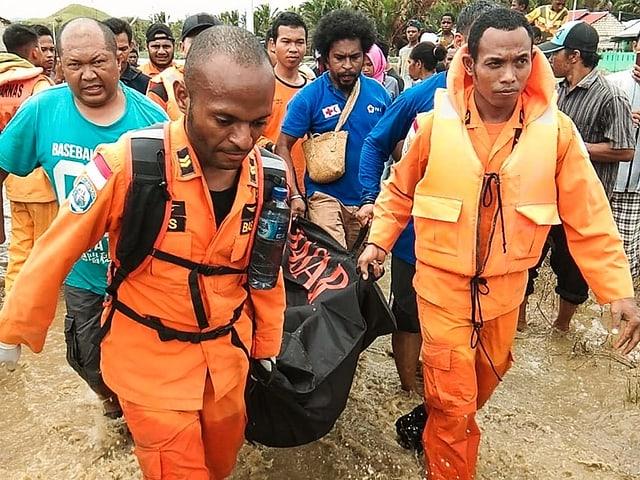 Rettungskräfte in orangen Anzügen tragen ein Opfer in einer Tasche.