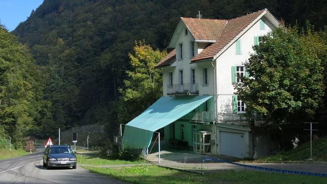 Ein grosses weisses Haus mit grünen Fensterläden.