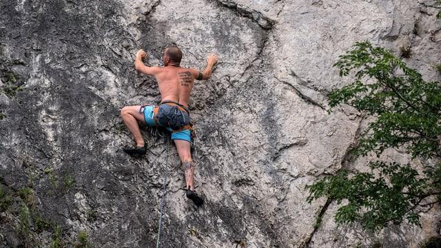 Ein Mann klettert am Fels.