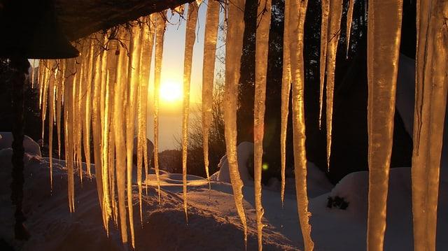 Leuchtende Eiszapfen, im Hintergrund verschneite Landschaft mit Sonnenuntergang.