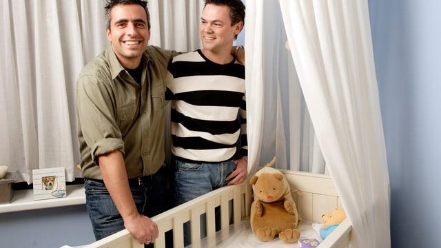 Eing gleichgeschlechtliches Männerpaar steht neben einem Kinderbettchen.