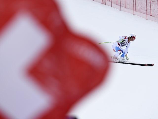 Die Schweizer Flagge verdeckt einen Skifahrer.