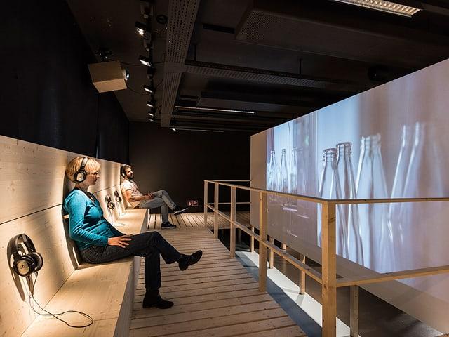 Besucher in einer Ausstellung sehen sich Flaschen auf einem Screen an.