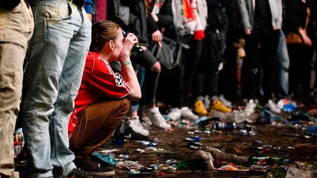 Eine Frau mit rotem Liverpool-T-Shirt kauert am Boden, um sie herum stehen Liverpool-Fans