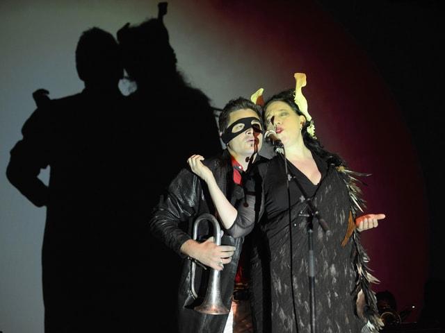 Eine Frau und ein Mann auf der Bühne. Er trägt eine Trompete und eine schwarze Maske. Sie ein schwarzes Federkleid.
