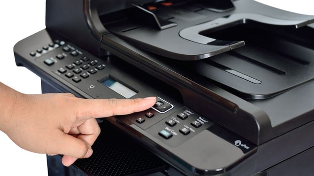 Eine Person drückt auf einen Knopf eines schwarzen Druckers.