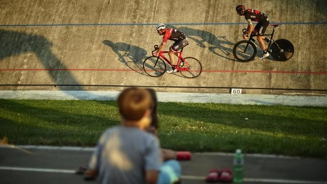 Zwei Radrennfahrer in einer Steilkurve, davor sitzt ein Junge, der zuschaut.