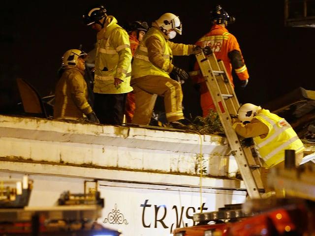 Einsatzkräfte der Feuerwehr mit einer Leiter auf dem Dach des betroffenen Pubs.