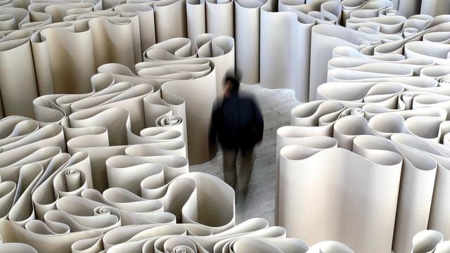 Mann geht durch ein Labyrinth aus hochkant aufgestellten Papierbögen.
