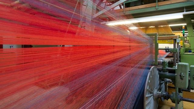 Rote Garnfäden laufen in eine Plüschwebmaschine.