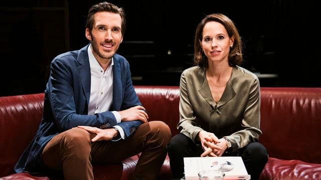 Ein Mann und eine Frau sitzen auf einem Sofa und blicken in die Kamera