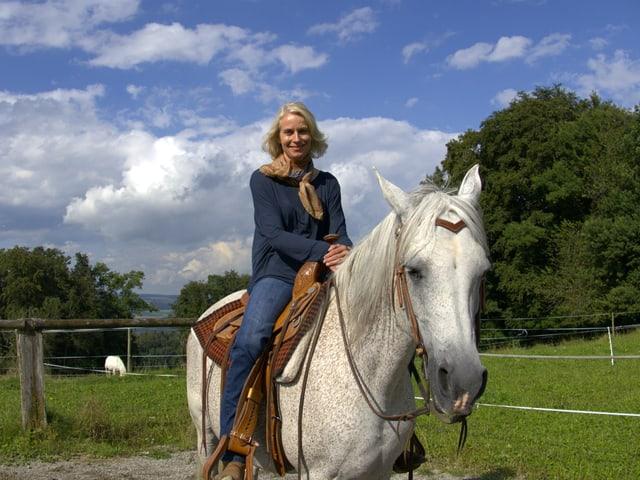 Béatrice auf einem Pferd.