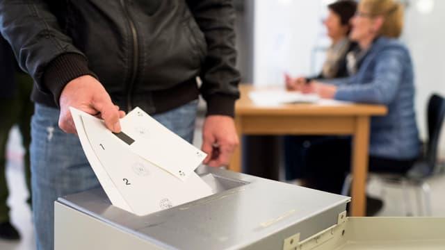 Ein Mann wirft im Wahllokal seine Stimmzettel in die Wahlurne