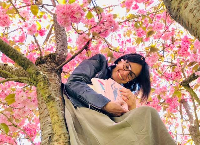 Annette König sitzt auf einem Kirschbaum mit einem Bücherstapel