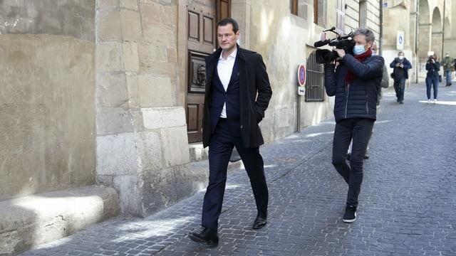 Mann läuft alleine durch Gasse. Ein Kameramann mit geschulteter Kamera folgt ihm.