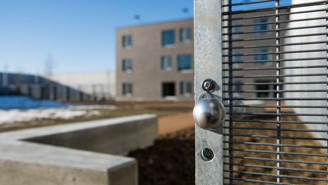Blick auf ein Gefängnisgebäude. Gittertor.