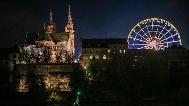 Blick in Basel auf Münster und violett-erleuchtetes Riesenrad.