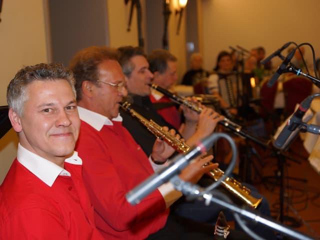 Mehrere Musiker nebeneinander beim Musizieren.