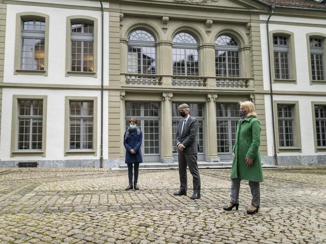 Drei Personen stehen auf Platz