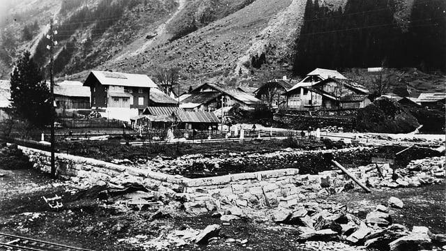 Schwarzweissfoto: Eine Baustelle vor einem Dorf.