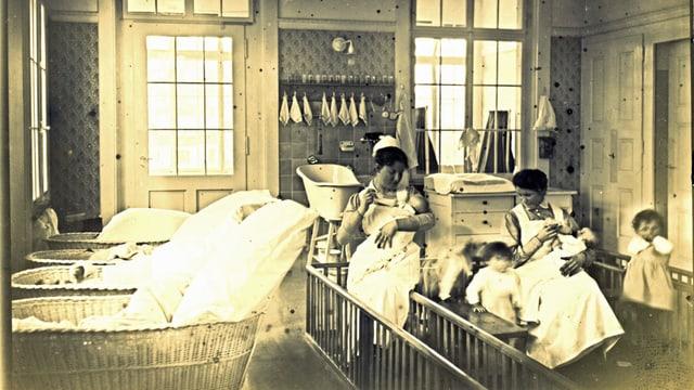 Aufnahme von ca. 1930, wo zwei Kinderpflegerinnen mit weissen Schürzen und Häubchen zwei Babys den Schoppen geben, während etwas grössere Kinder um sie herum springen.