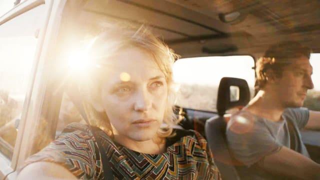 Ein Paar Sitzt in einem Auto. Sie schaut aus dem offenen Fenster.
