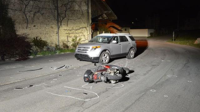 Das Auto mit dem verunfallten Motorroller auf der Strasse. Kreidezeichnungen markieren die UnfallSituation