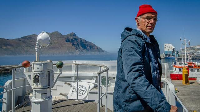 Cousteau steht auf seinem Schiff und starrt in die Ferne.