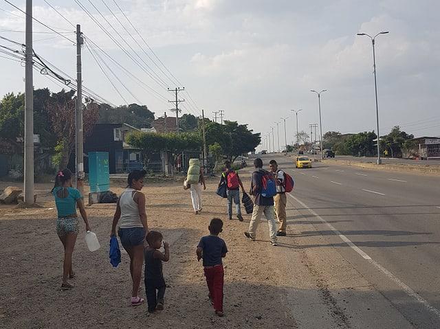 Eine Gruppe Venezolaner laufe neben einer Strasse. Es sind junge Eltern mit ihren Kindern.