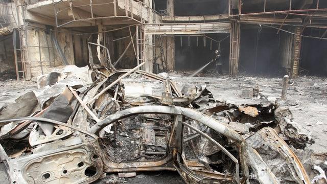 zerstörtes Auto vor zerstörtem Haus