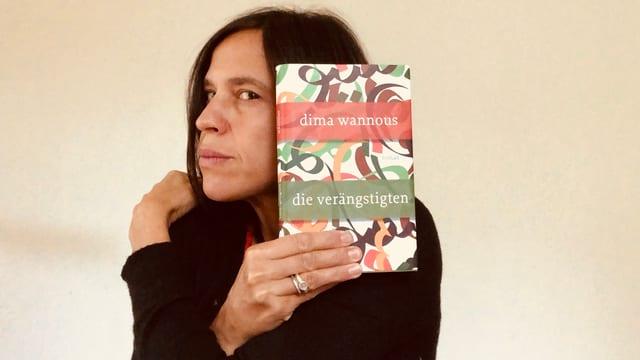 Annette König umarmt sich selbst und hat dabei den Roman «Die Verängstigten» von Dima Wannous in der Hand