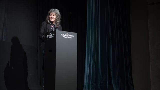Eine Frau hält auf einem Podium eine Rede