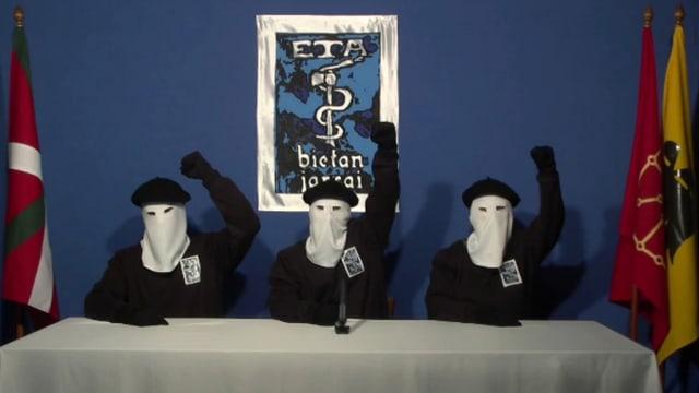 Drei ETA-Mitglieder mit weissen Masken strecken die Fäuste in die Luft.