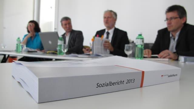 Im Vordergrund ist scharf zu sehen der Sozialbericht, ein grau-weisses dickes gebundenes Buch, mit ein wenig rot. Im Hintergrund unscharf zu sehen, die vier Teilnehmer der Mediekonferenz, unter anderem Peter Gomm.