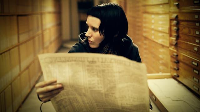 Eine junge Frau mit schwarzen Haaren läuft durch ein Archiv und hält eine Zeitungsseite in der Hand.