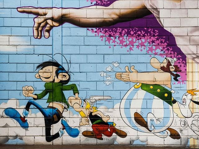 Drei Comicfiguren auf einer Hauswand.