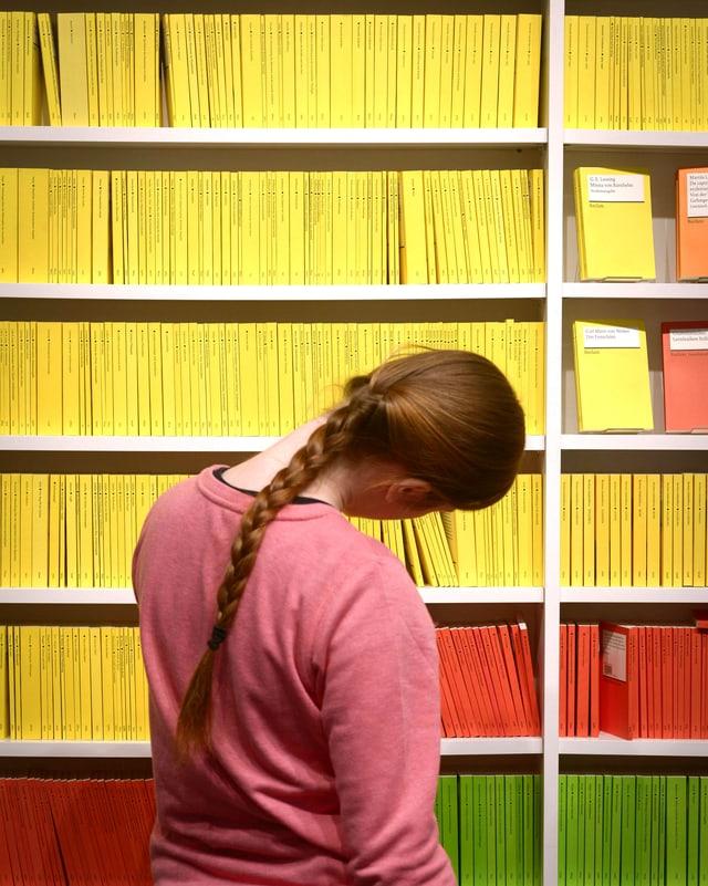 Eine Studentin vor einem Buchregal mit Reclams.