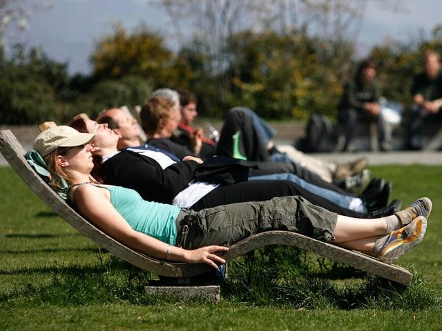 Leute liegen in leichter Kleidung auf Liegestühlen.