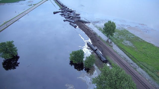 Luftaufnahme des verunglückten Zuges mit Waggons im Wasser.