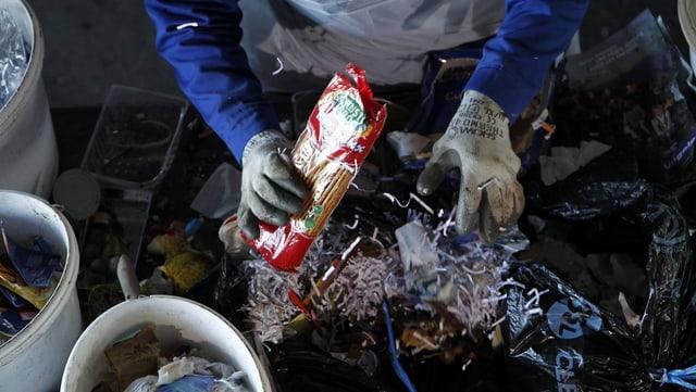 Ein Arbeiter wühlt in einem Abfallsack.