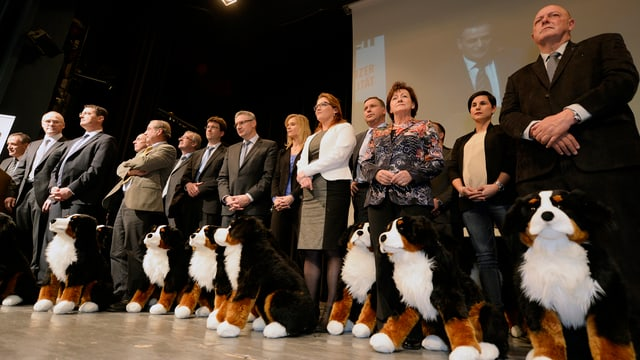 Alle Kandidierenden in Reih und Glied mit Stoff-Hund vor den Füssen