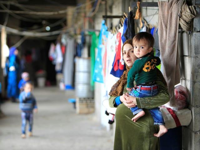 Eine schwangere Syrerin mit einem Kind auf dem Arm.