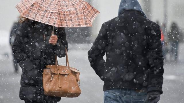 Zwei Personen gehen im Schneesturm durch die Stadt, die Frau hält einen Schirm. Die Gesichter sind nicht zu sehen.