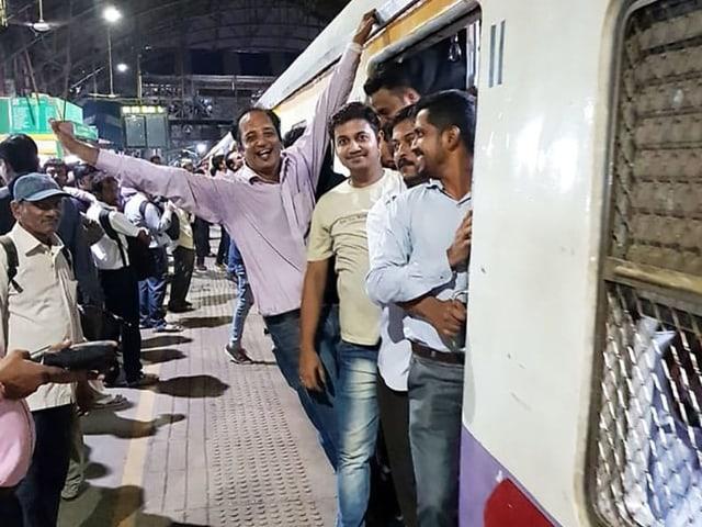 Mehrere Indische Männer stehen in der offenn Tür eines Zuges in Mumbai. Der Zug steht noch im Bahnhof. Die Männer lachen in die Kamera, einer posiert voller Freude mit einem ausgestreckten Arm, während er sich am Zug festhält.