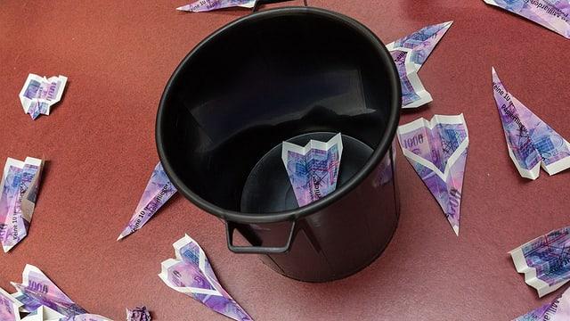 Papierflieger aus «Tausendernoten» landen in einem Abfalleimer.