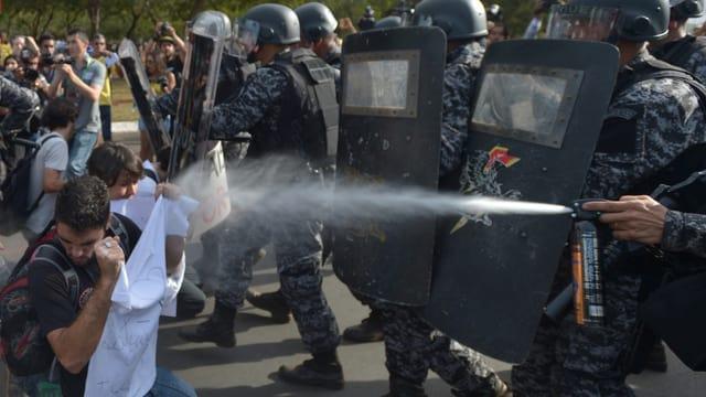 Polizisten gehen mit Tränengas gegen Demonstranten vor.