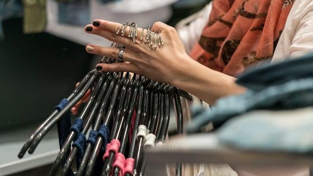 Frauenhand hält viele Kleiderbügel mit T-Shirts